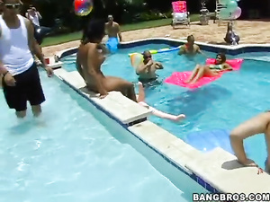 Beautiful young chicks and sexy muscled guys are having party by the pool
